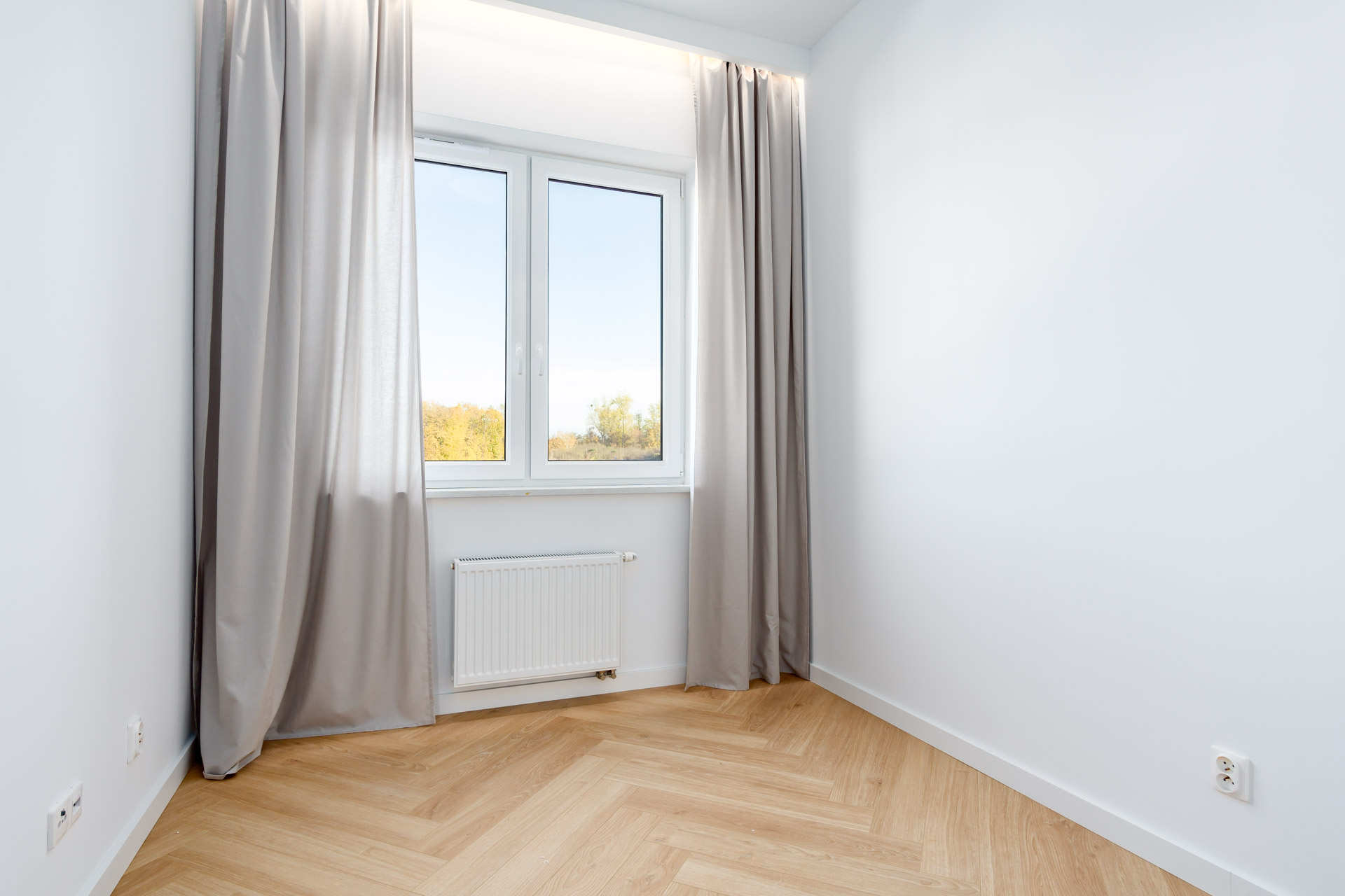 Sypialnia w nowym bloku z podłogą w jodełkę